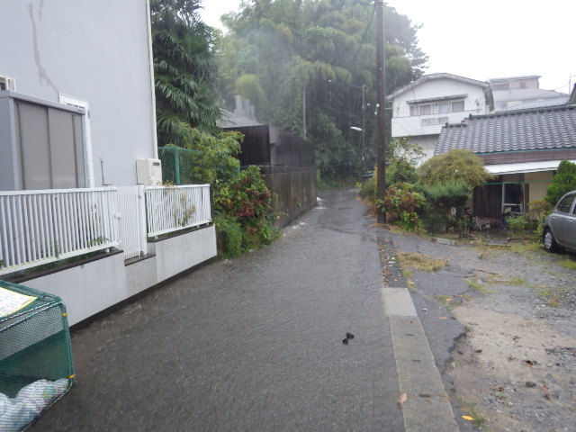 山からの雨水があふれ出した道路(向かって左側が排水の悪い側溝)